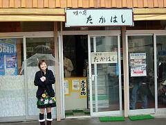 味の店たかはしの入り口に立つ記者